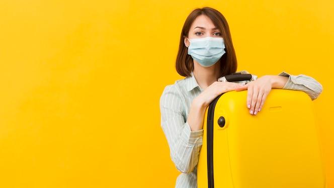 Женщина, носящая медицинскую маску, держа ее желтый багаж
