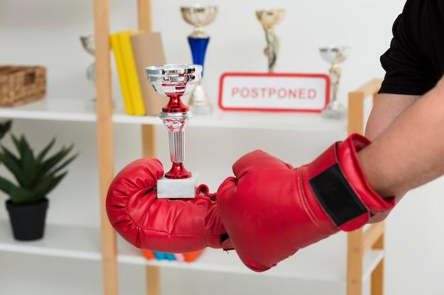Человек с боксерскими перчатками держит трофей