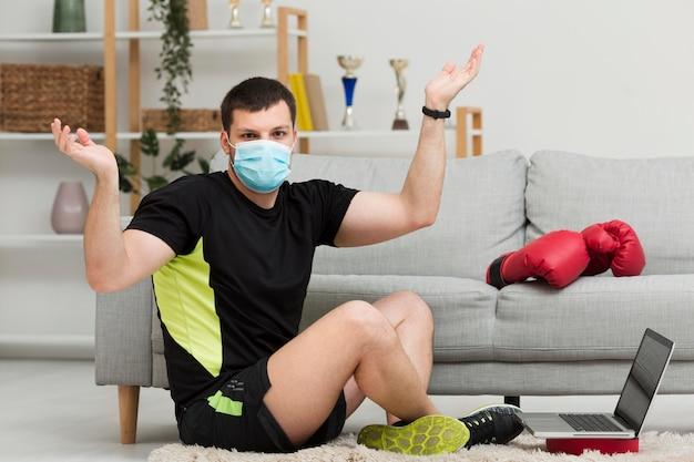 ロングショットの男性が医療用マスクを着用しながらトレーニング