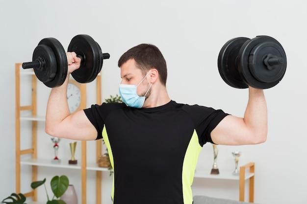 Человек тренируется дома во время ношения медицинской маски