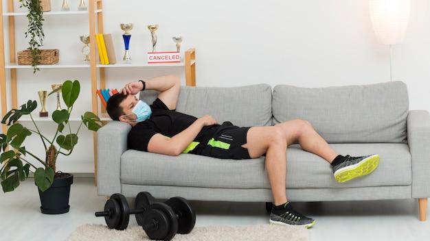 Человек отдыхает на диване во время ношения спортивной одежды и маски для лица