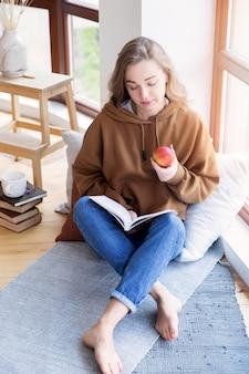 Высокий угол красивой женщины, чтение книги