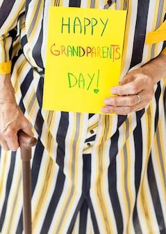 Крупным планом бабушка держит сообщение годовщины