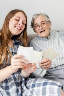 Бабушка смотрит на старые фотографии с внучкой
