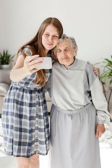 Внучка принимает селфи с бабушкой