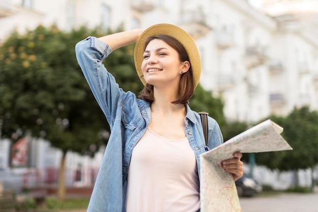 旅行に満足して帽子を持つ若い女性