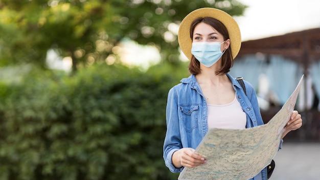 医療マスクと地図を正面から見た旅行者