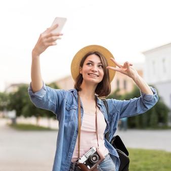 Счастливая женщина в шляпе, принимая селфи на праздник