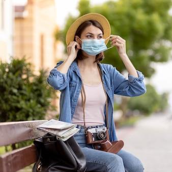 屋外のフェイスマスクを持つ女性の肖像画