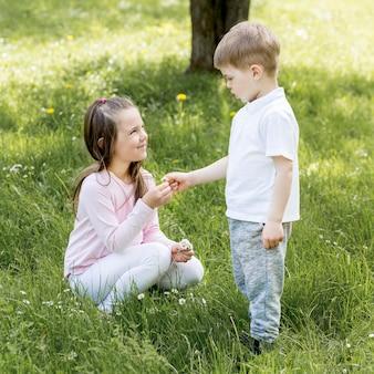 兄と妹が芝生で遊んで