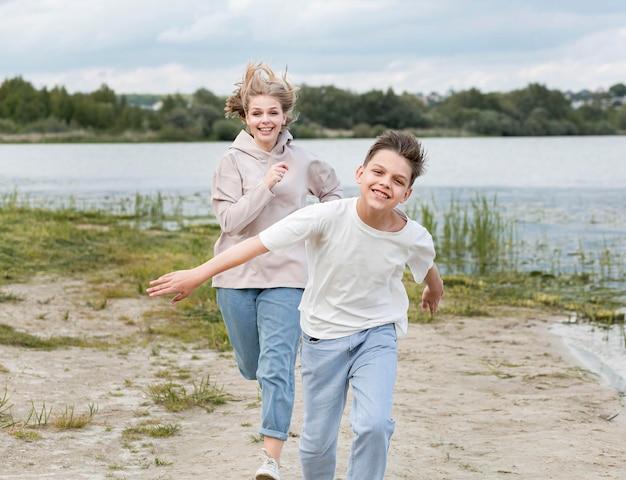 砂の上に彼女の息子と一緒に走っているお母さん