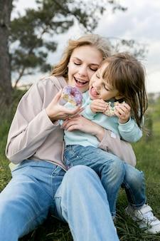Мать и ребенок едят пончики