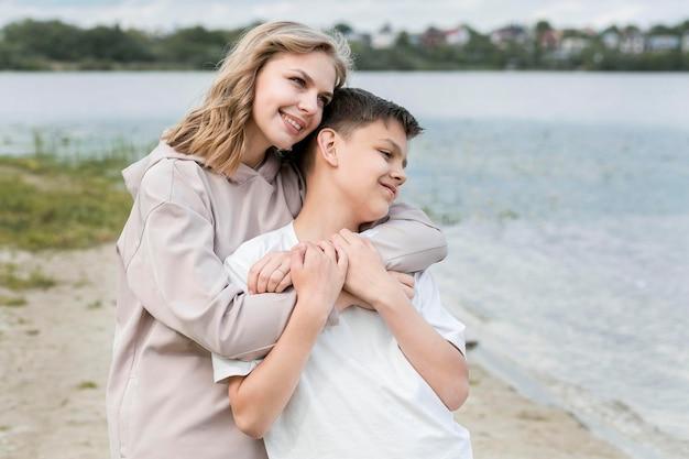 Мальчик на улице и мама обнимаются на берегу озера