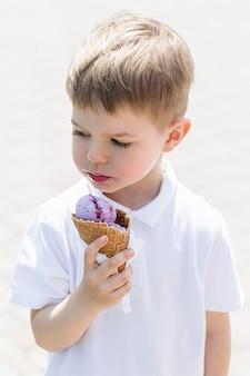 Мальчик на улице ест мороженое