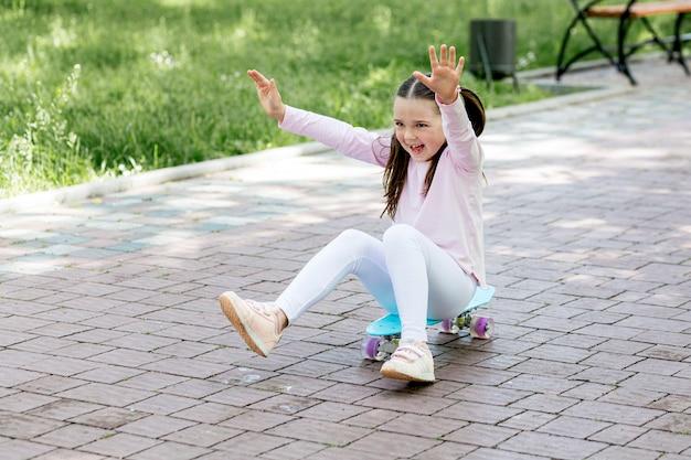 Малыш на улице играет со скейтбордом