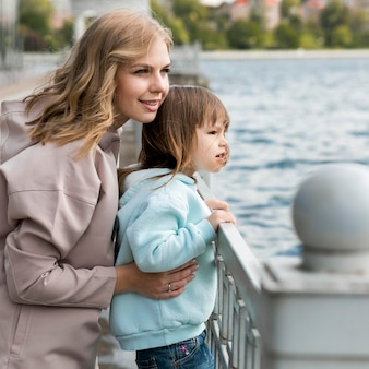 屋外の若者と湖を見てママ