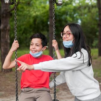 老眼鏡とフェイスマスクを持つ子供を持つ母