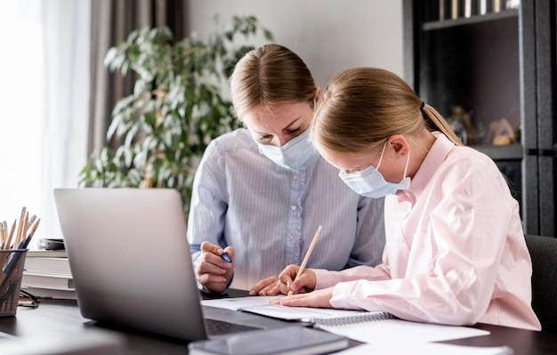 Женщина помогает молодой девушке с домашней работой во время ношения медицинской маски