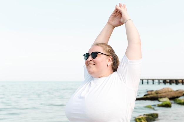 Женщина на пляже делает упражнения на растяжку