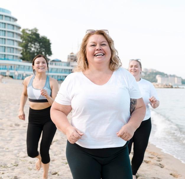 Возбужденные молодые друзья бегают по пляжу