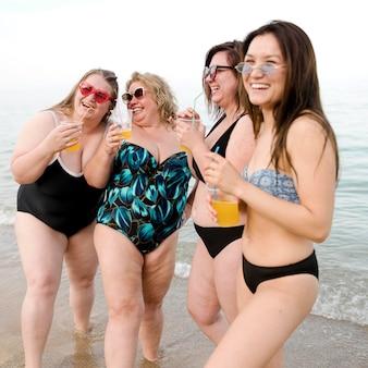 ビーチでジュースを飲む女性