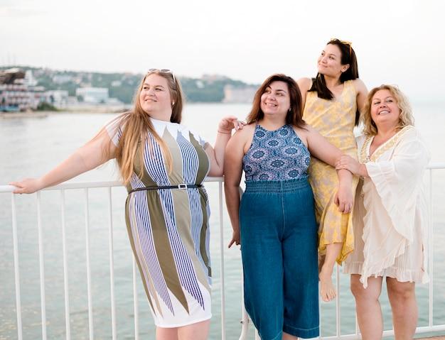 Женщины в повседневной одежде опираются на забор