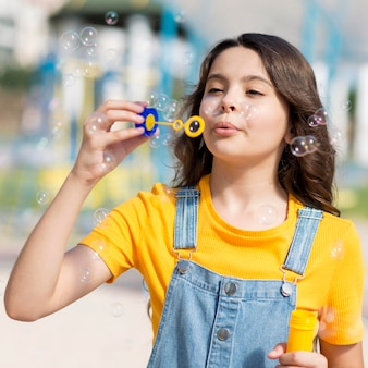 Девушка играет с воздуходувкой пузыря