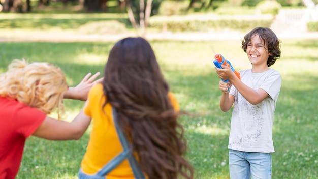 Дети играют с водяной пушкой