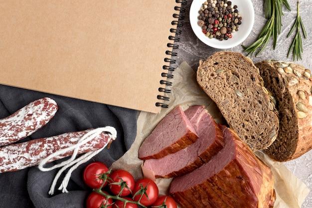 Филе мяса с помидорами и хлебом рядом с блокнотом