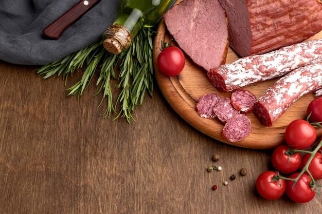 机の上の木の板にサラミとフィレ肉