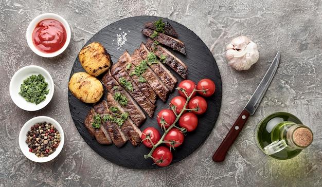 机の上のソースとトップビューおいしい調理肉
