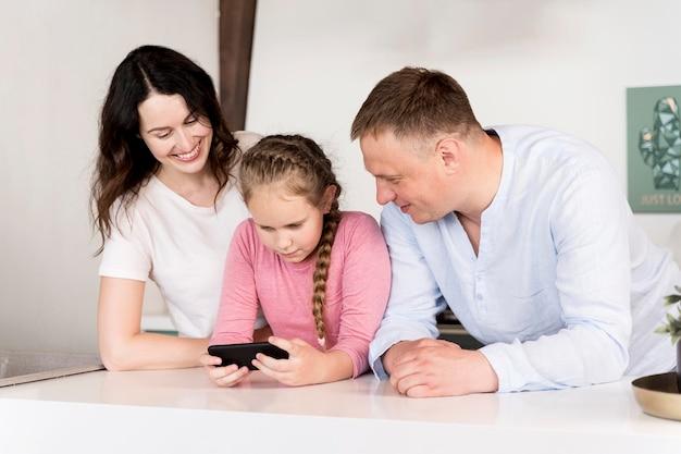 Средний снимок родителей и малыша с телефоном