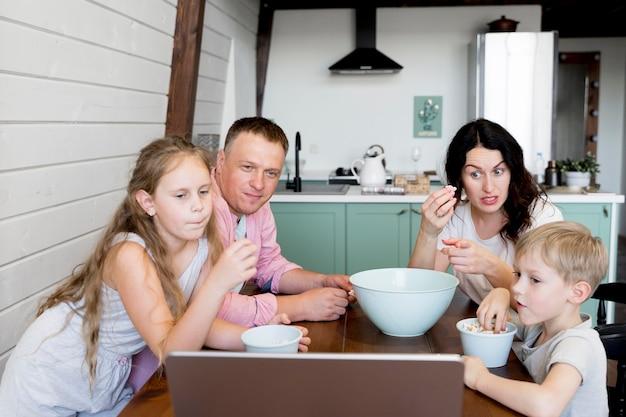 Средняя семья, сидящая за столом