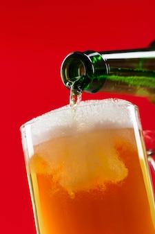 グラスにビールを注ぐクローズアップ
