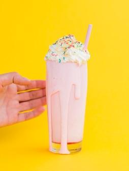 黄色の背景とピンクのミルクセーキ