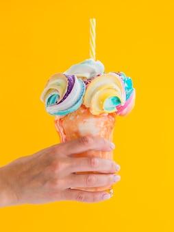 Макро рука держит красочный молочный коктейль