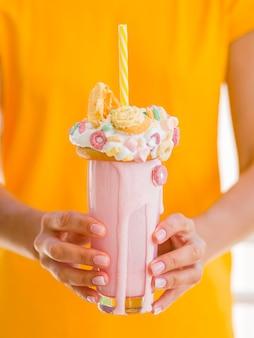 Макро руки держат молочный коктейль