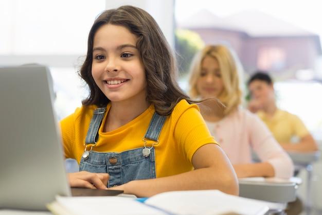 学校でラップトップを持つ少女