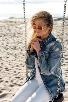 Женщина сидит на качелях на пляже