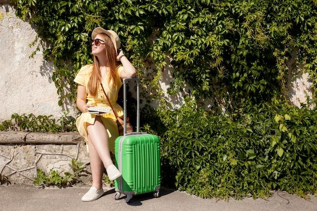 荷物を持って座っているフルショットの女性