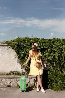 緑の荷物を持つフルショットの女性