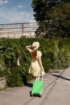 荷物を持って歩くフルショットの女性
