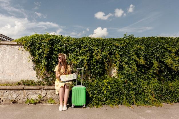 地図を保持しているフルショットのスマイリーの女の子