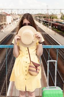帽子を保持している正面図女性