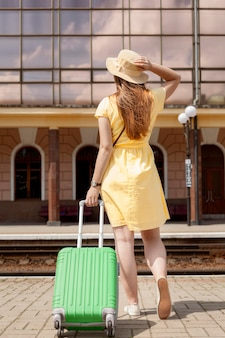 手荷物を保持している背面図女性