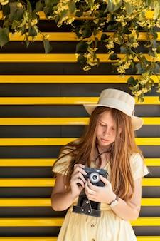 Девушка вид спереди с фотоаппаратом