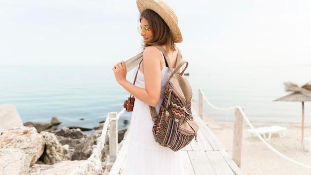 Боковой вид женщина позирует на пляже