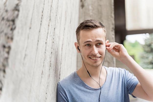 音楽を聴くイヤホンを持つ男性