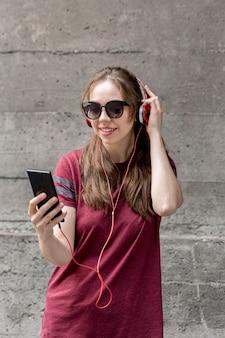 Женщина портрета с музыкой солнечных очков слушая