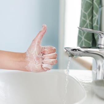 Человек показывает палец вверх во время мытья рук в ванной комнате